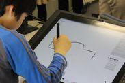 「Wacom Cintiq 21UX ペンタブレット」でデータをスケッチする子ども