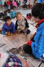 大学生から凧の作り方を聞く子供たち。