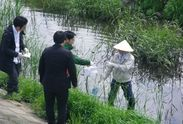 川で微生物を採取する山下教授と研究員の様子