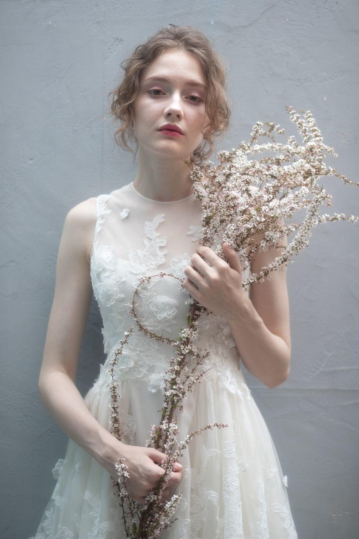 1c9010a81ee24 ウェディングドレスの持つ魔法のような高揚感を大切にしながら「モダンロマンティック」をコンセプトに、繊細なレースやフラワーモチーフを贅沢にあしらったドレスが  ...