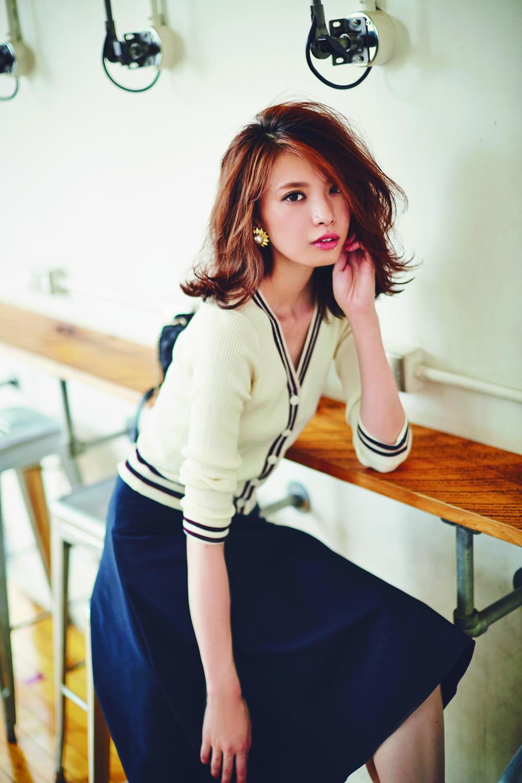 白いカーディガンに紺のスカートを合わせた上品なファッションの宮田聡子