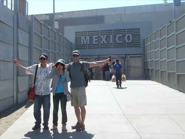 アメリカ・サンディエゴにてメキシコとの国境付近で記念写真を撮る旅行者